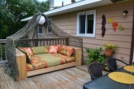 łóżko wykonane z palet stojące w ogrodzie